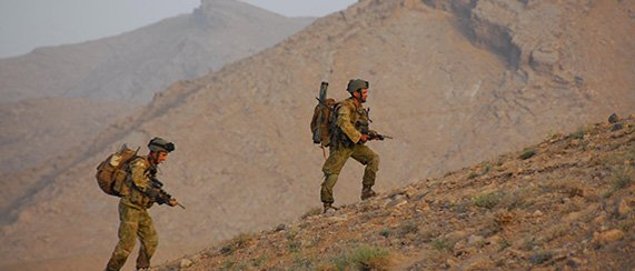 two army soldiers walking up a hill in an arid area